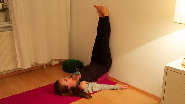 Unterstützter Schulterstand gegen die Wand