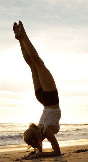 Frau am Strand macht den Unterarmstand