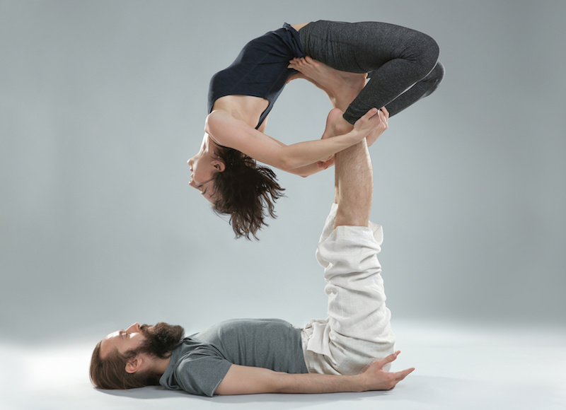 Young couple practicing yoga on light background